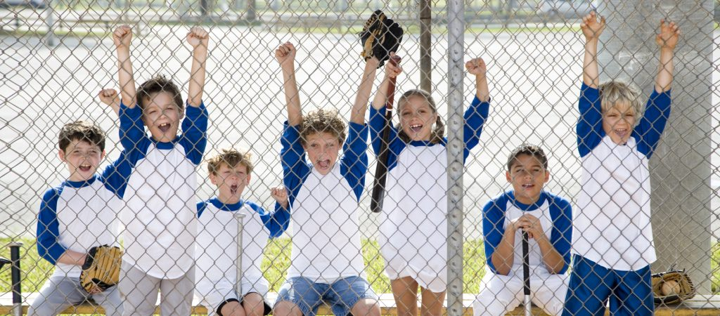 Little league baseball team cheering behind wire fence